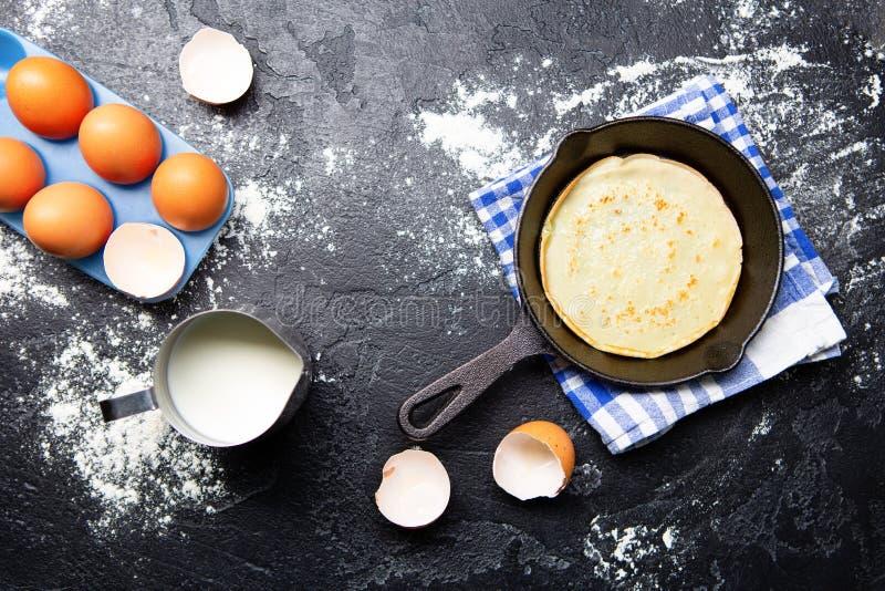 Image sur des oeufs, lait, casserole avec les cr?pes, serviettes sur la table noire image stock