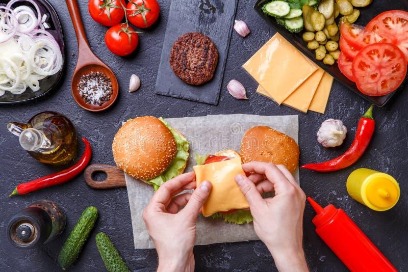 Image sur deux hamburgers, mains humaines et ingrédients images stock