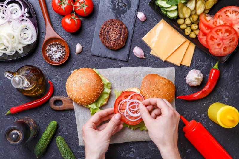 Image sur deux hamburgers, mains humaines et ingrédients photos stock