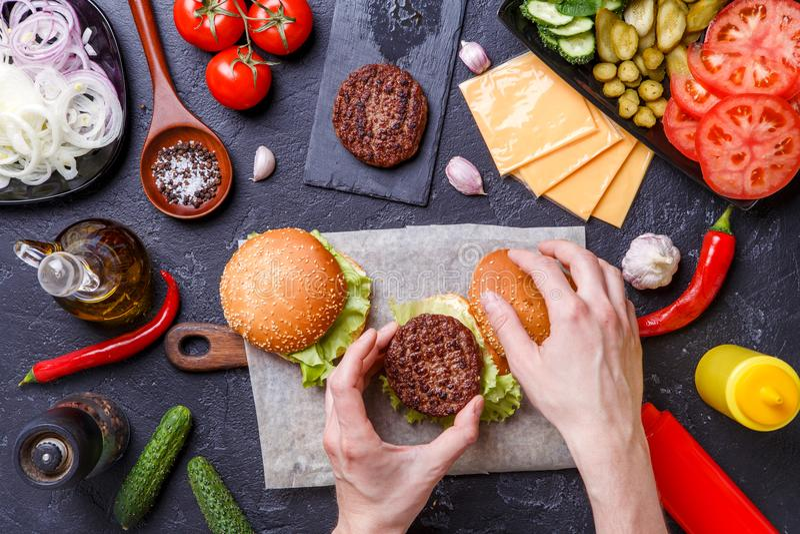 Image sur deux hamburgers, mains humaines et ingrédients photo libre de droits