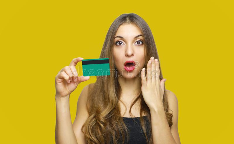 Image of surprised young lady standing over yellow background and holding debit card in hands. Looking at camera royalty free stock image