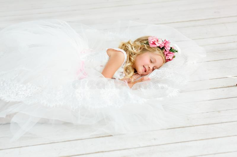 Image of sweet baby girl in a wreath from fresh pink flowers lying on the floor in a beautiful white dress. stock images