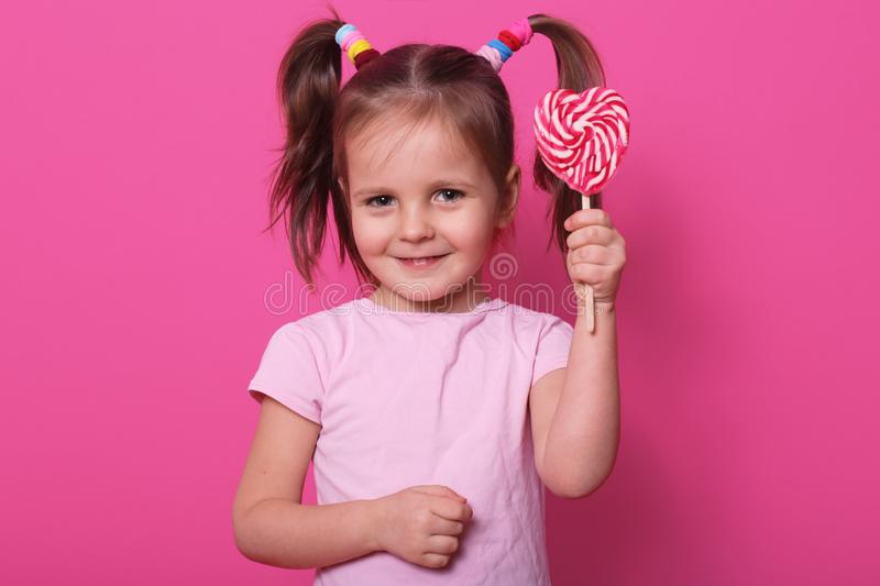 Image of sweet beautiful female child holding big lollipop candy, looks happy and excited  over pink background, little royalty free stock photos
