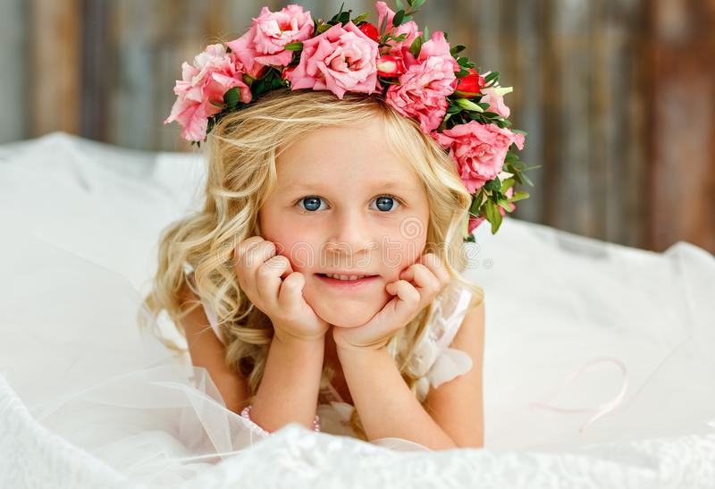 Image of sweet beautiful little girl with white hair wearing a natural flower crown. Large portrait. Looking at the stock image