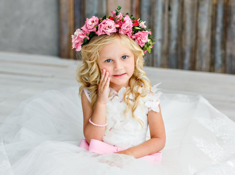 Cute little girl with blonde hair in a bright studio with a wreath of pink flowers. Looking at the camera and smiling royalty free stock photography