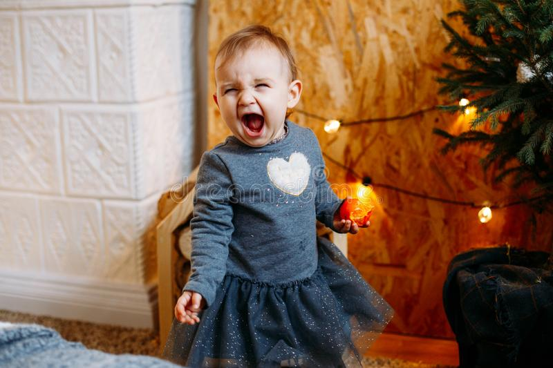 Image of sweet and cute baby girl in grey dress, portrait of beautiful 1 year old smiling child, toddler. Happy girl in stock image