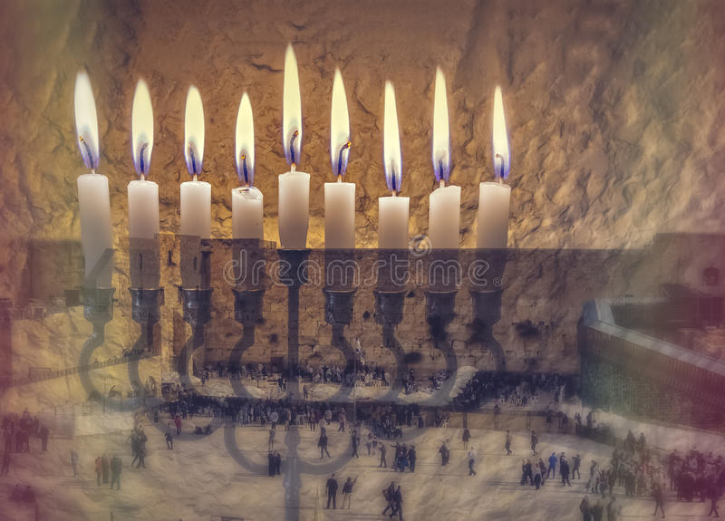 The image symbolizes Hanukkah Holiday and Jewish desires and hopes. Composite image of menorah with glittering candles and western wall in Jerusalem. The image royalty free stock images