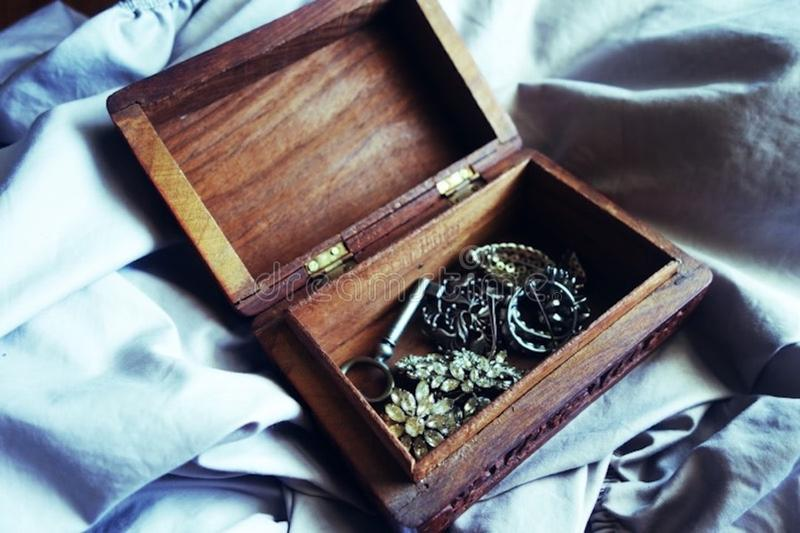 Overhead of wooden jewellery box filled with vintage brooches royalty free stock photos