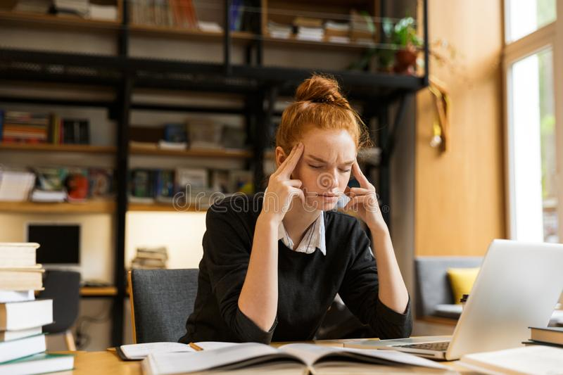 Image of tense concentrated woman studying, while sitting at desk in college library with bookshelf background royalty free stock photos