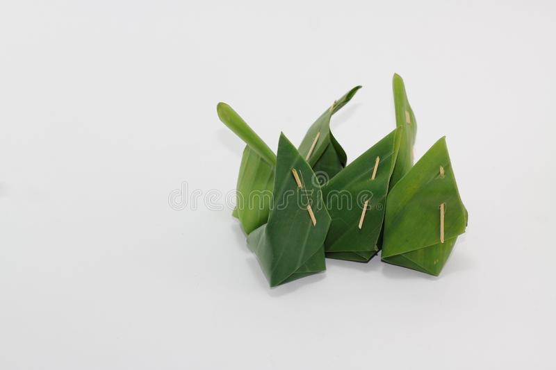 Thai desserts wrapped in banana leaves with a white background. Image of Thai desserts wrapped in banana leaves with a white background royalty free stock photo