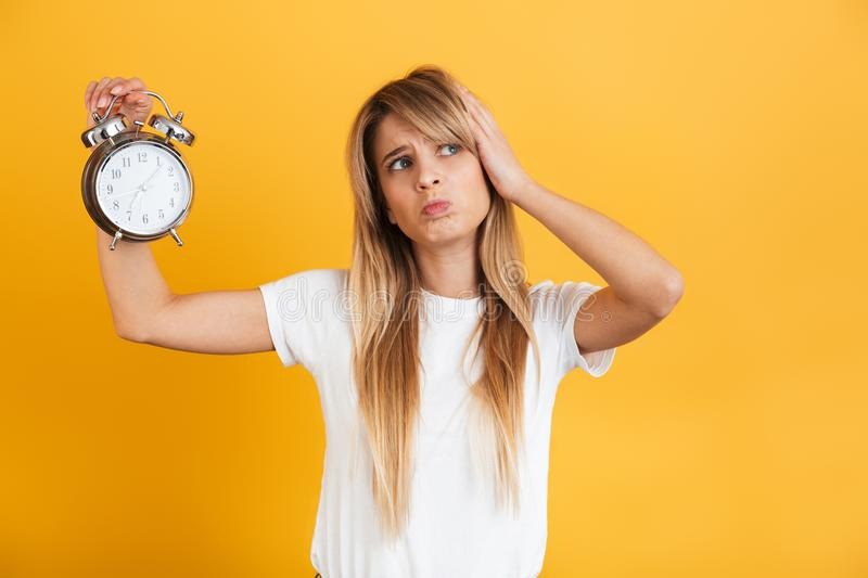 Thinking serious young blonde woman posing isolated over yellow wall background dressed in white casual t-shirt holding alarm stock photo