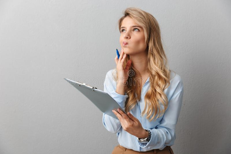 Thinking young pretty blonde business woman posing  grey wall background holding clipboard. Image of a thinking young pretty blonde business woman posing  grey stock image