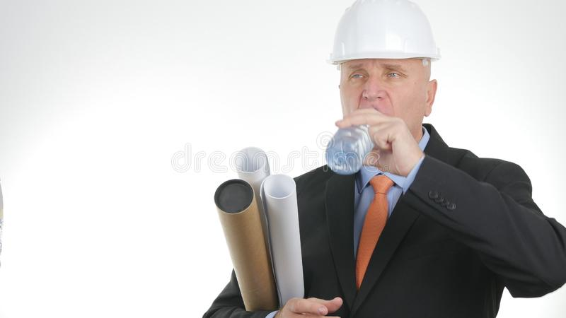 Image with a Thirsty Engineer Drinking Fresh Water from a Bottle royalty free stock photography
