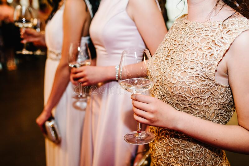 The image of three girls holding wine glasses. Party stock photos