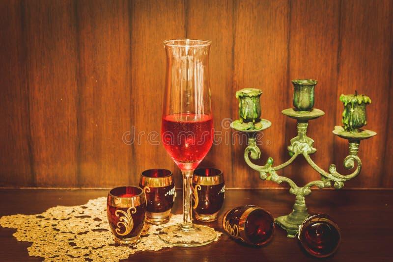 Image toujours de la vie du vin rouge et du chandelier au-dessus du backgro en bois photo stock