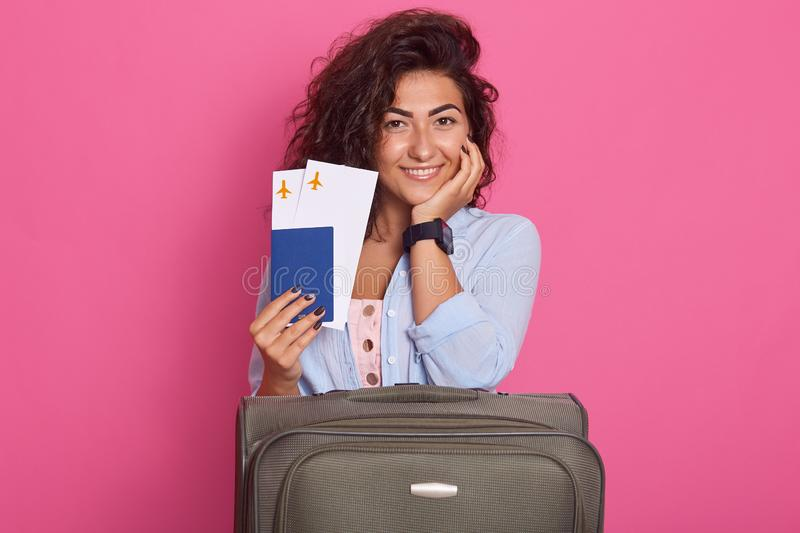 Image of tourist woman in casual clothes, hat holding passport, tickets isolated on rose background. Female traveling abroad, stock photography