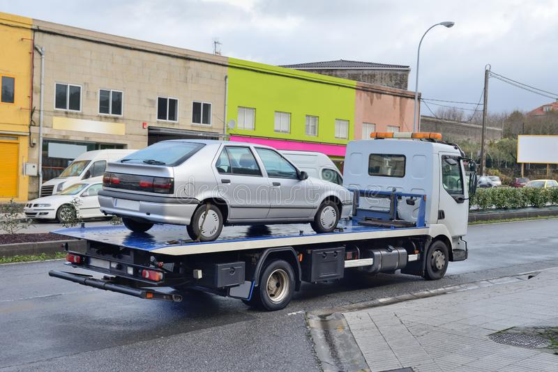 Tow truck with a car on the road. Image of tow truck with a car on the road stock photos