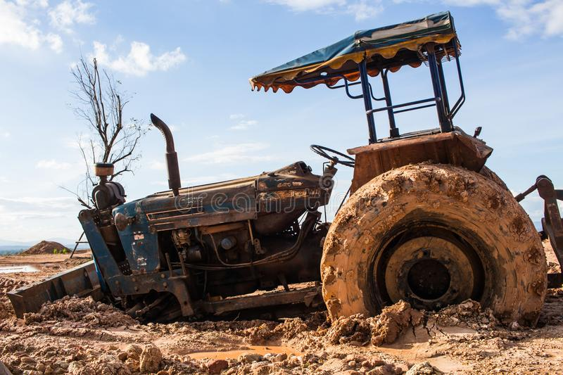 The image of the tractor in the mud stock photo