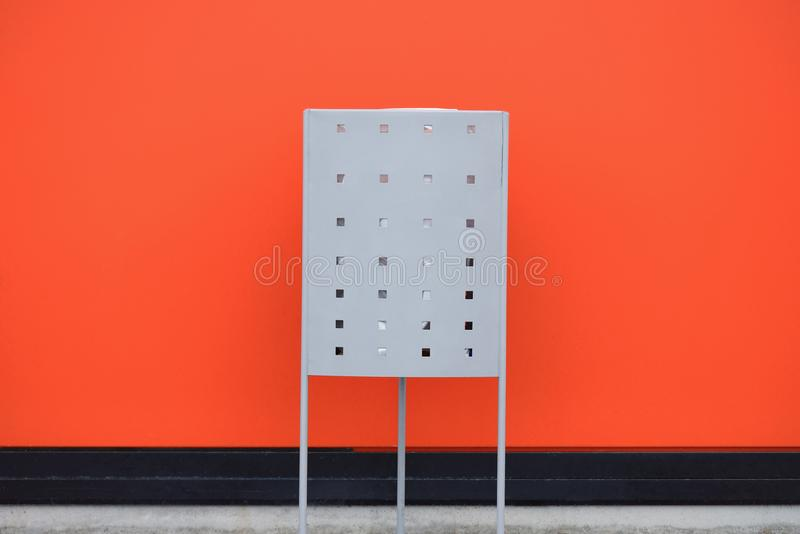Trash can on the background of an orange wall stock photo