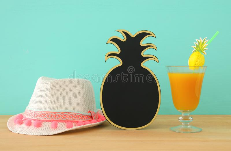 Image of tropical and exotic fruit coctail, blank pineapple blackboard for copy space next to white fedora hat over wooden table. royalty free stock photos