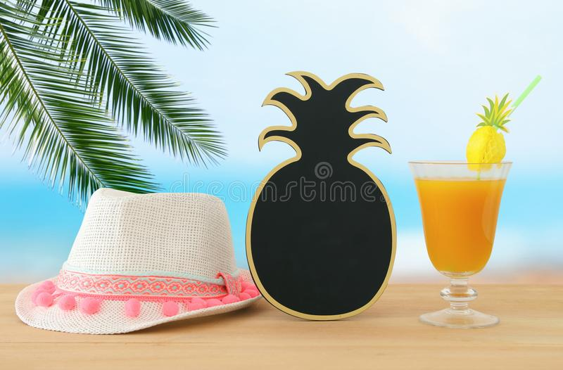Image of tropical and exotic fruit coctail, blank pineapple blackboard for copy space next to white fedora hat over wooden table. royalty free stock photography