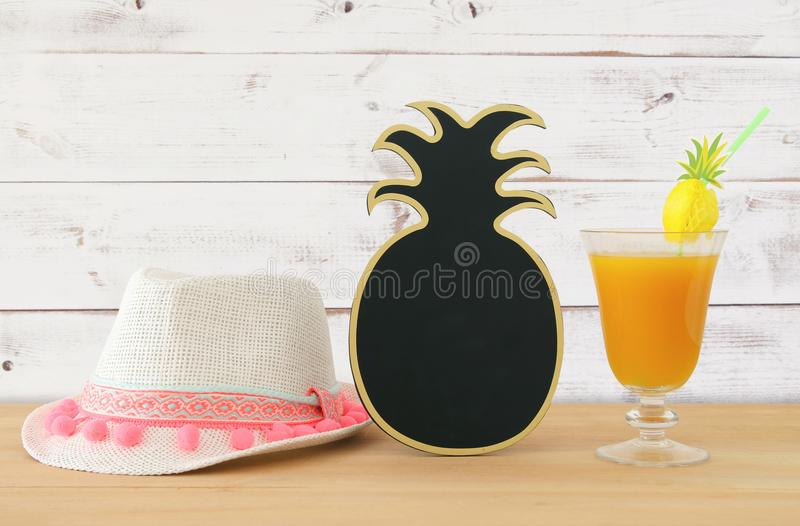 Image of tropical and exotic fruit coctail, blank pineapple blackboard for copy space next to white fedora hat over wooden table. royalty free stock photo