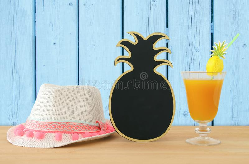 Image of tropical and exotic fruit coctail, blank pineapple blackboard for copy space next to white fedora hat over wooden table. stock photography