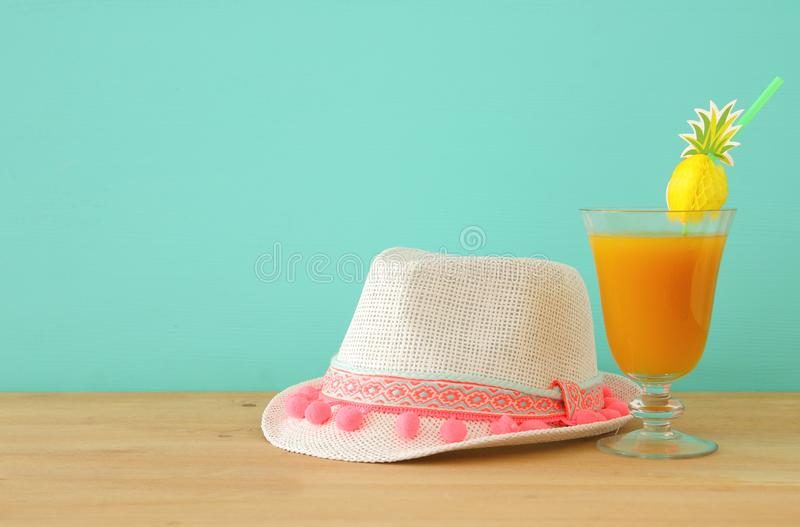 Image of tropical and exotic fruit coctail next to white fedora hat over wooden table. stock photography