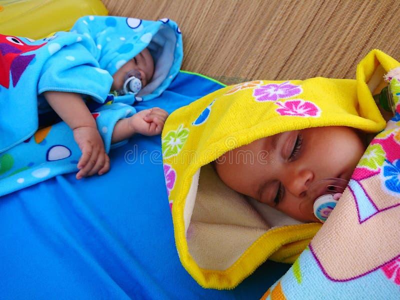 Twin babies sleeping on the beach. stock photo