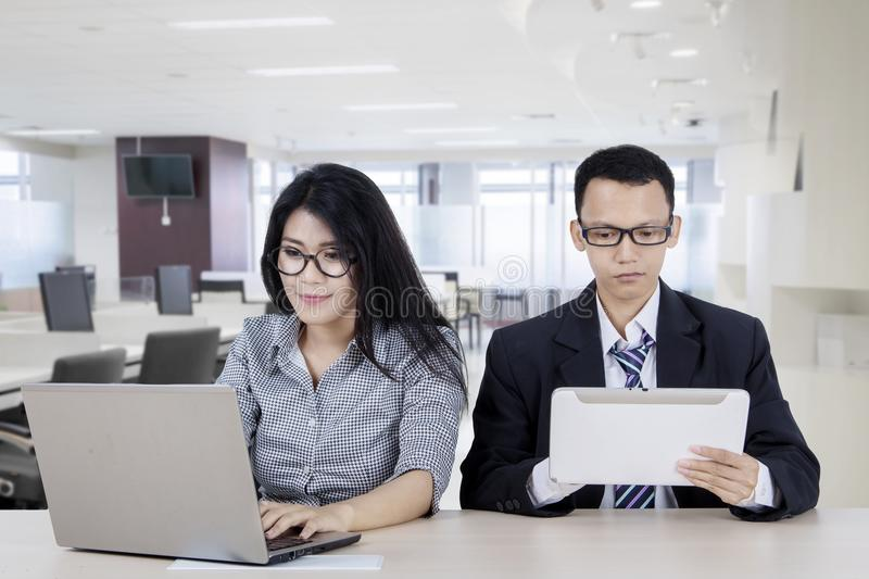 Two business people using digital device royalty free stock photography
