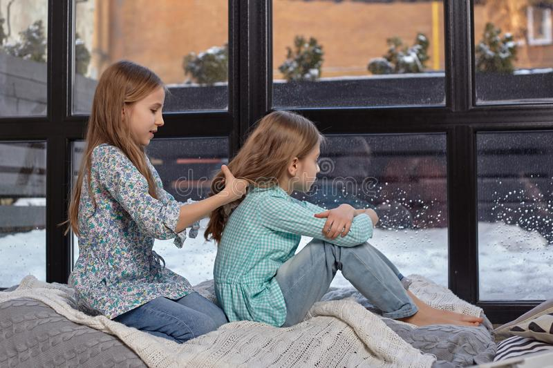 The image of two cute little sisters sitting on windowsill in peace and quiet. Two beautiful caucasian sisters sitting on the windowsill, they look out of the stock image