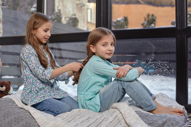The image of two cute little sisters sitting on windowsill in peace and quiet. Two beautiful caucasian sisters sitting on the windowsill, they look out of the royalty free stock photos