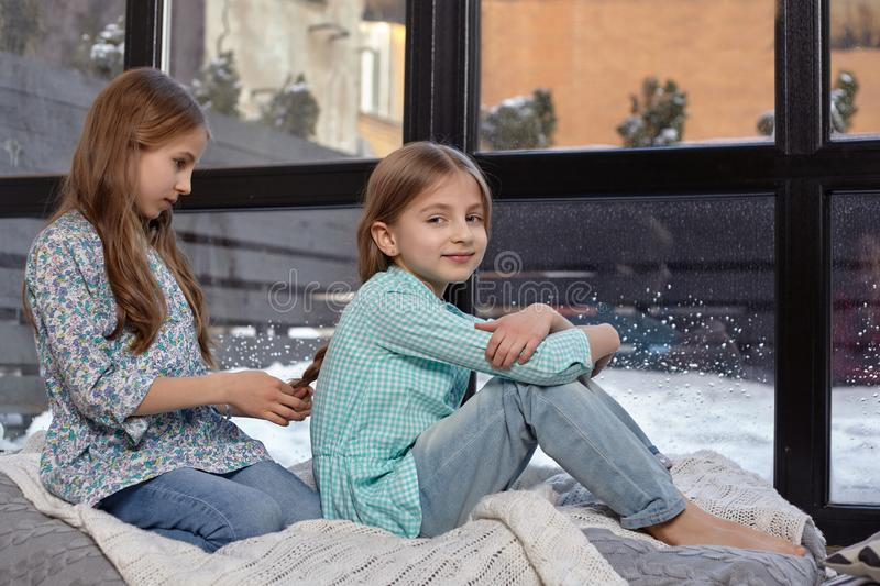The image of two cute little sisters sitting on windowsill in peace and quiet. Two beautiful caucasian sisters sitting on the windowsill, they look out of the royalty free stock images