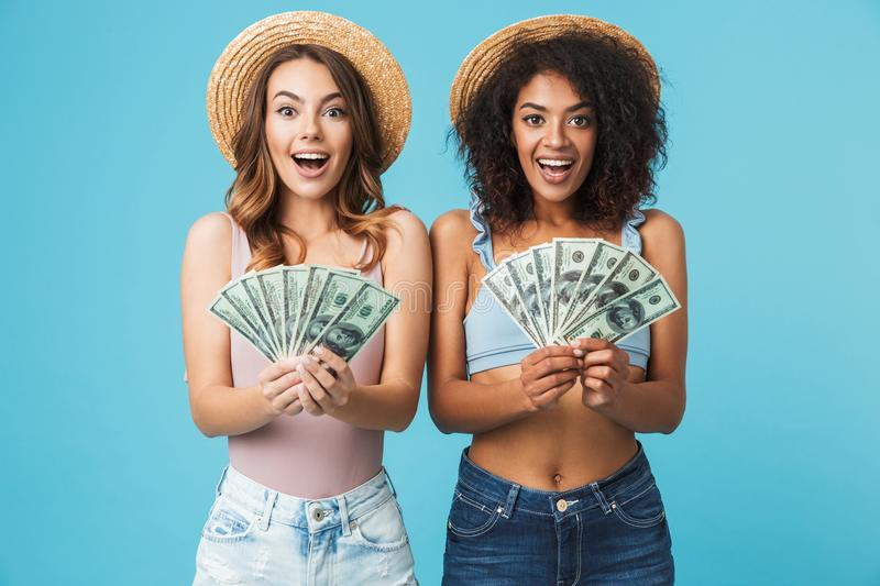 Image of two delighted girls 20s with different type of skin wearing straw hats rejoicing and holding fans of dollar banknotes, i royalty free stock photos