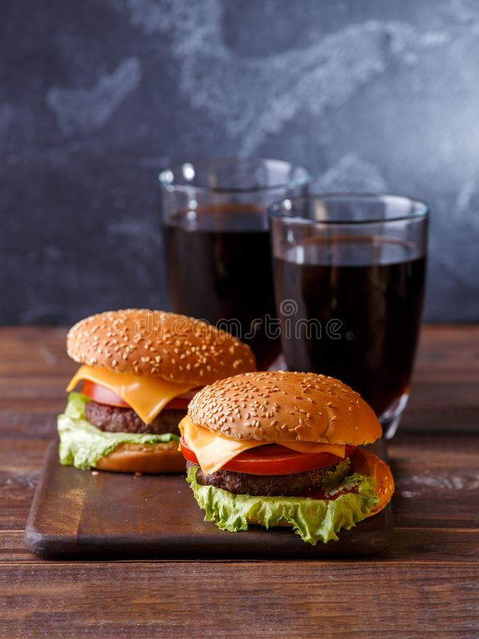 Image of two fresh hamburgers and two glasses of juice royalty free stock photos