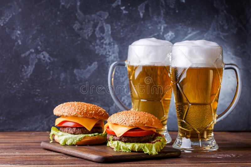 Image of two hamburgers, glasses with beer. On wooden table stock photos