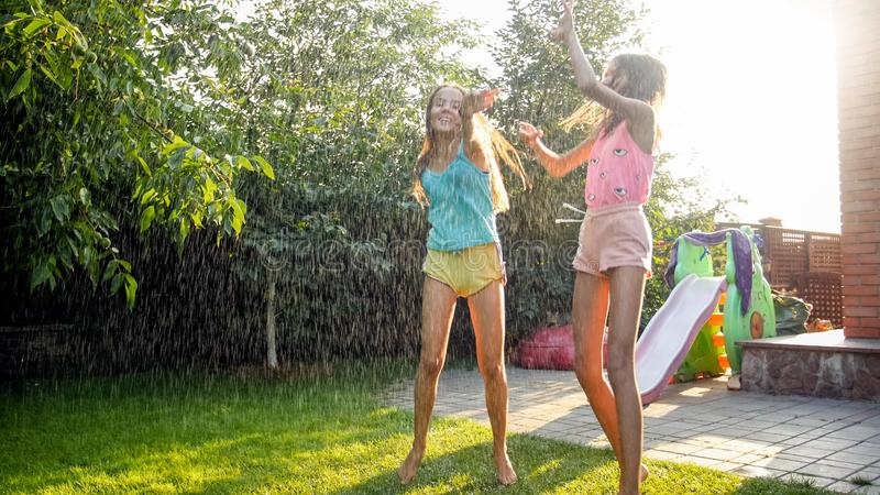 Image of two happy laughing teenage girls jumping and dancing under warm summer rain at house backyard garden. Family royalty free stock images