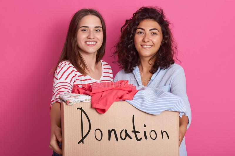 Image of two pretty brunette girls wearing red striped and blue shirts, presenting box with vivid clothes preparing for commission stock image
