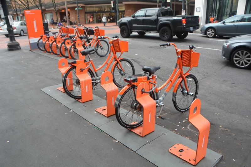 Orange bikes for rent and traffic in Portland, Oregon. This is an image of two rows of orange bikes made available for the public to rent in downtown Portland stock photos