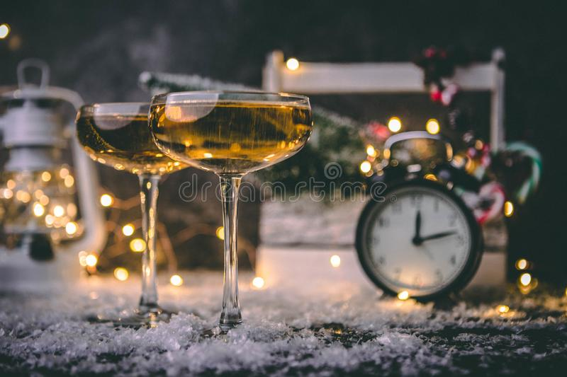 Image of two wine glasses on blurred background with Christmas tree, lantern, clock royalty free stock photography