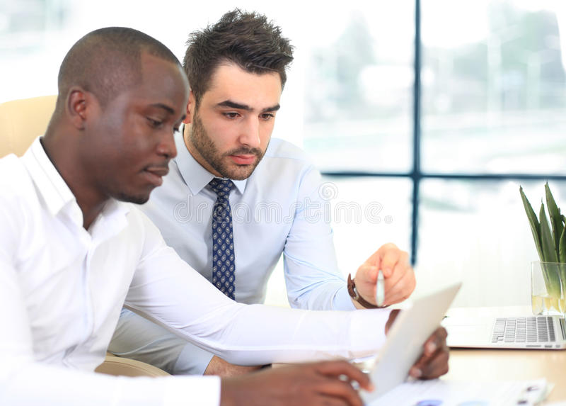 Image of two young businessmen. Interacting at meeting in office stock image