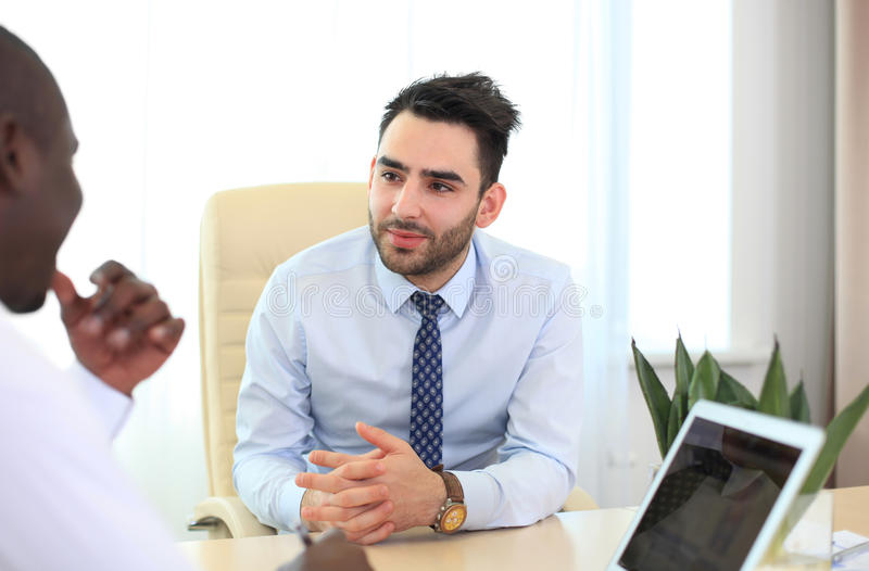 Image of two young businessmen. Interacting at meeting in office royalty free stock image