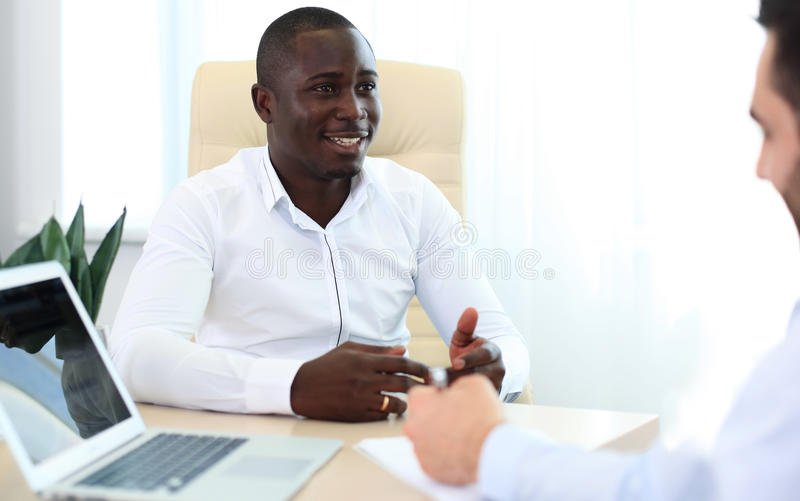 Image of two young businessmen. Interacting at meeting in office stock images