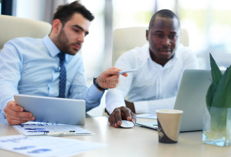 Image of two young businessmen. Interacting at meeting in office royalty free stock photo