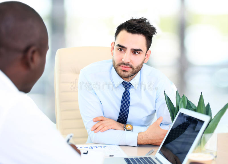 Image of two young businessmen. Interacting at meeting in office stock photography