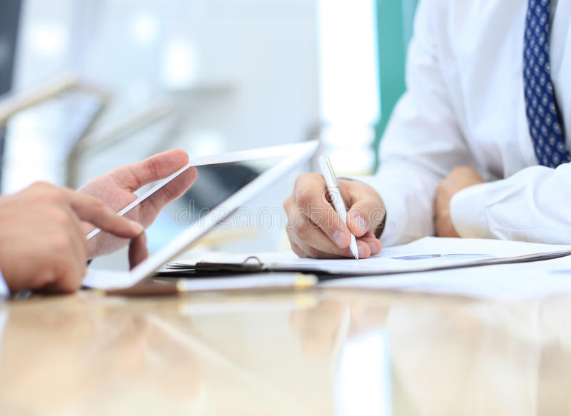 Image of two young businessmen. Using touchpad at meeting stock photo