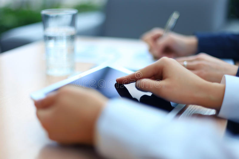 Image of two young businessmen. Using touchpad at meeting royalty free stock photo