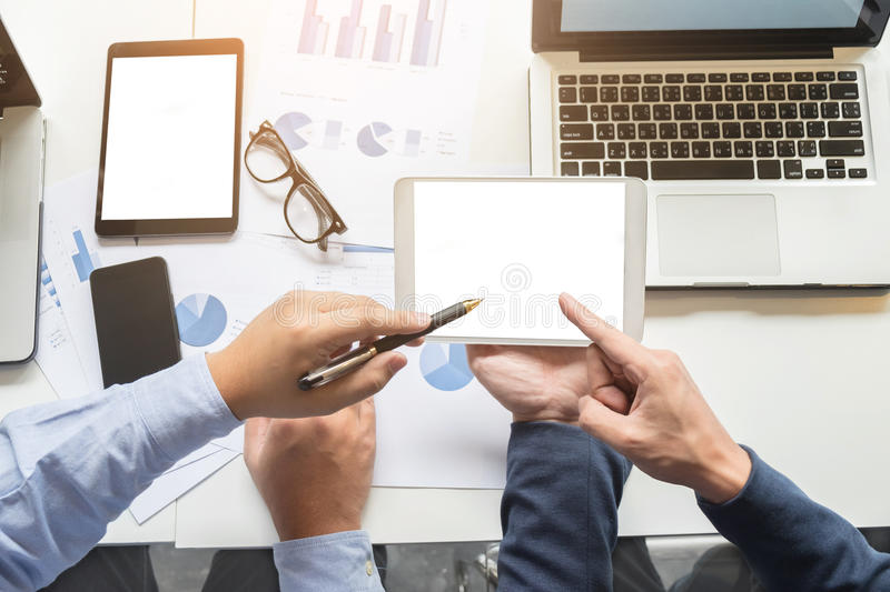 Image of two young businessmen working with laptop, tablet, smartphone and financial document data graph on table in office. royalty free stock images