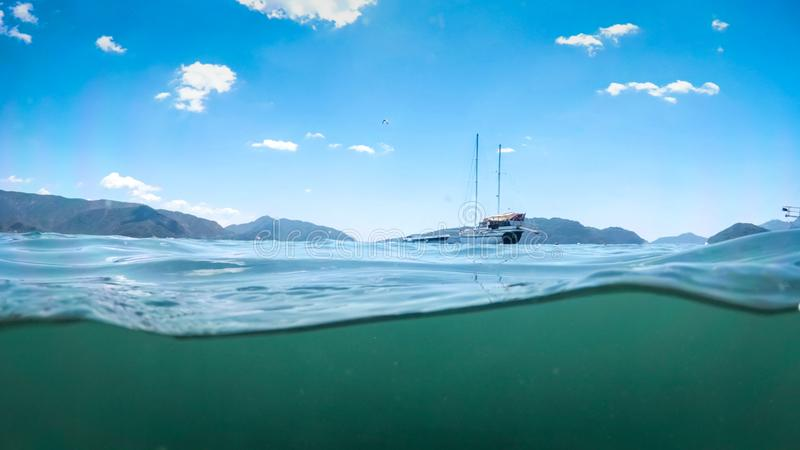 Image from under the water of yacht in sea against beautiful mountains stock image