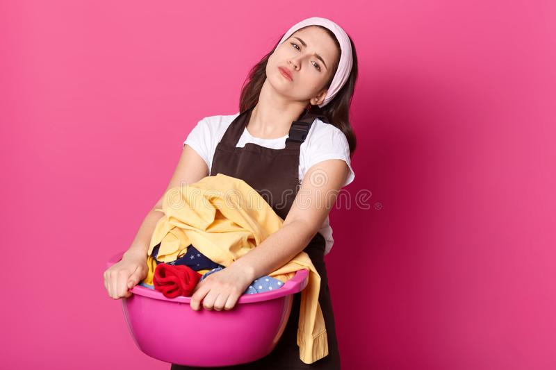 Image of upset European woman holds basin with dirty clothes, wears brown apron, has upset facial expressions, prepares for royalty free stock photography